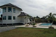 House for sale Na Jomtien showing the house garden and pool