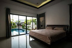 House for sale Na Jomtien Pattaya showing the master bedroom poolside